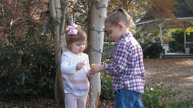 Ett yngre och ett äldre barn som pratar med varandra.